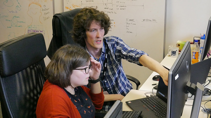 Matthew and his colleague discussing code