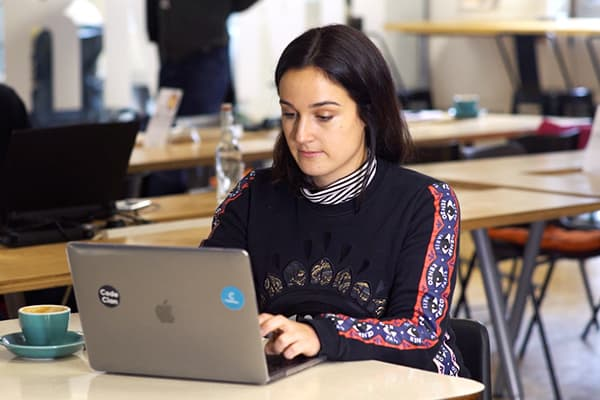 Kirstin sits typing on a laptop