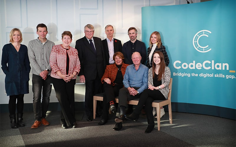 The CodeClan board standing and sitting in front of a CodeClan banner