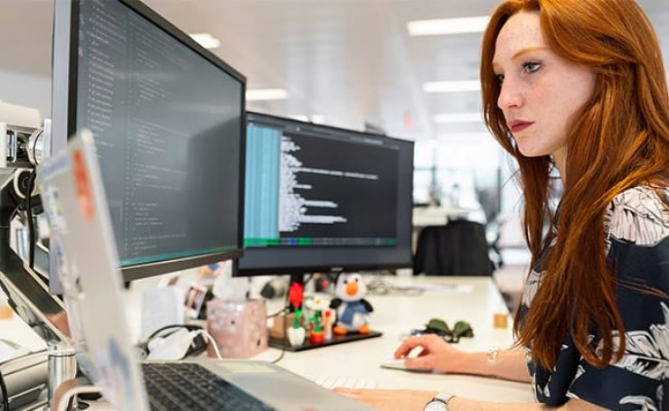 Woman coding in front of three screens in an office